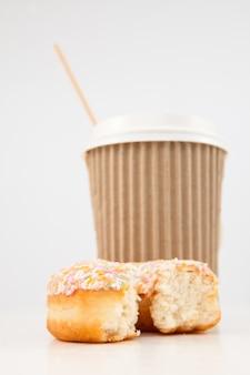Um donut meio comido e uma xícara de chá juntos
