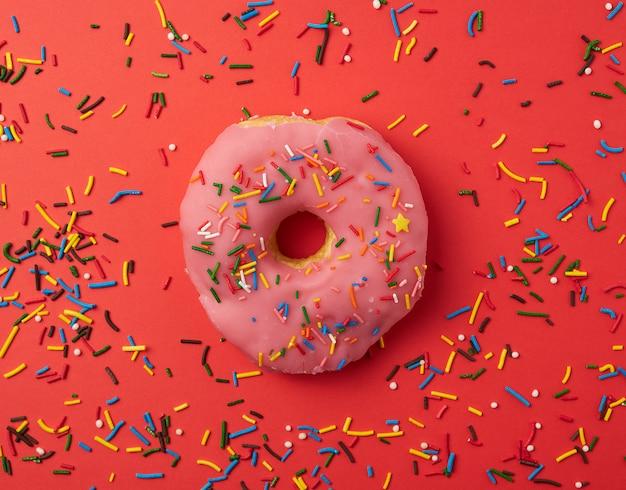 Um donut redondo rosa com granulado colorido sobre um fundo vermelho