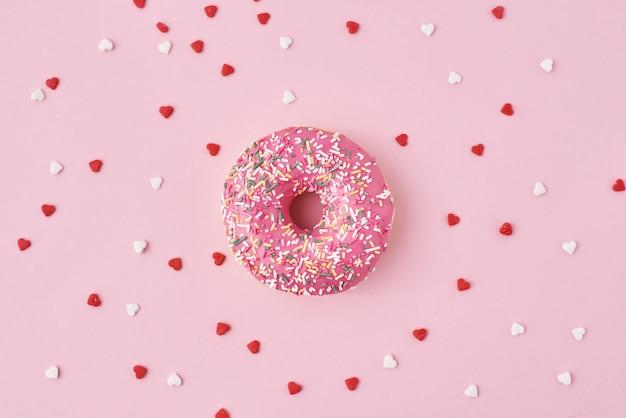Um donuts decorados glacê e confeitos e confetes em forma de coração no fundo rosa