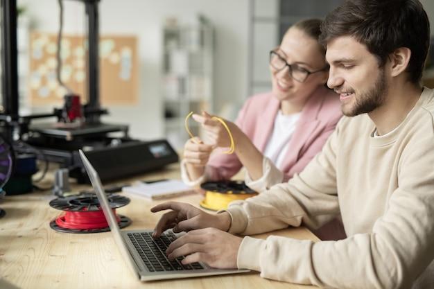 Um dos designers criativos sentado em frente ao laptop e rede enquanto seu colega escolhe o filamento para impressão 3d