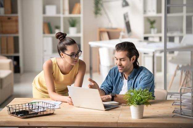 Um dos dois jovens corretores explicando os dados financeiros on-line de seu colega na tela do laptop durante o trabalho em equipe na reunião