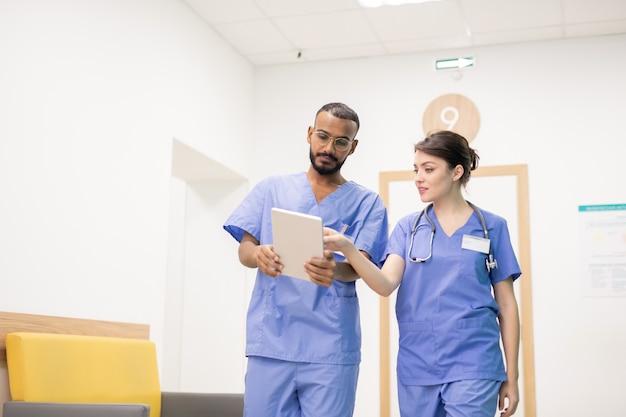 Um dos jovens médicos bem-sucedidos apontando para a tela do tablet digital enquanto faz uma apresentação ou explica algo a um colega