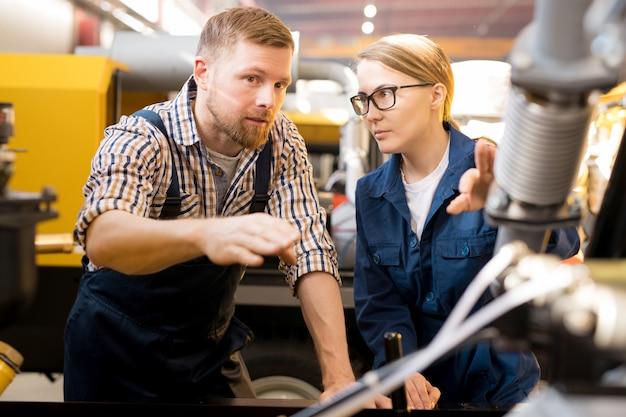 Um dos jovens técnicos confiantes apontando para o mecanismo do equipamento industrial durante a discussão de suas qualidades com o colega