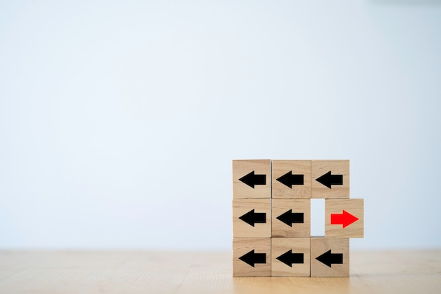 Um dos movimentos da seta vermelha para a direção oposta com os outros a seta preta que esculpiu em cubos de blocos de madeira para a interrupção dos negócios e o conceito de ideia de pensamento diferente.