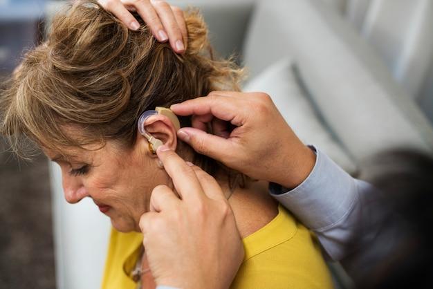 Um, doutor, inserindo, ajuda auditiva, para, um, paciente, orelha