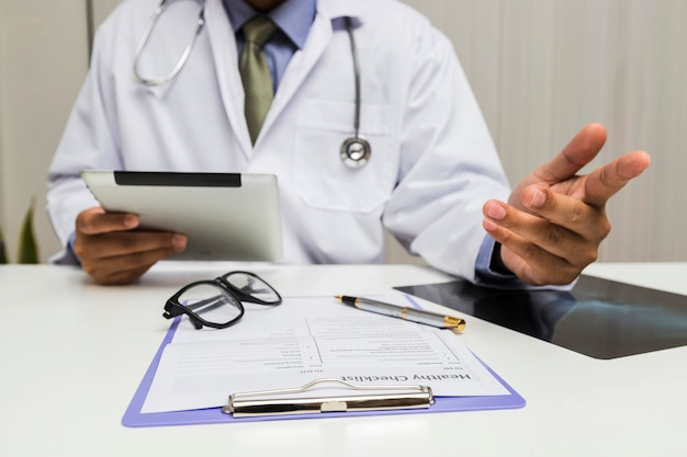 Um doutor que prende uma tabuleta e consulta o paciente no escritório.