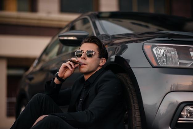 Um elegante empresário fuma charutos perto de um carro de luxo. moda e negócios
