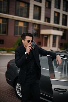 Um elegante empresário fuma charutos perto de um carro de luxo. moda e negócios.