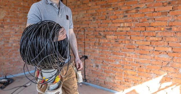 Um eletricista com capacete olha para a parede enquanto segura um cabo elétrico