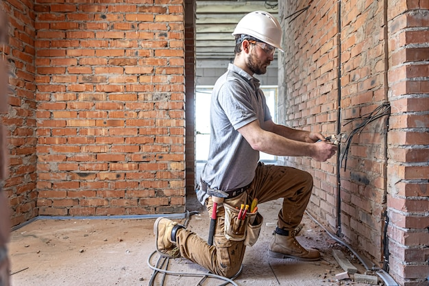 Um eletricista de construção corta um cabo de tensão durante um reparo.