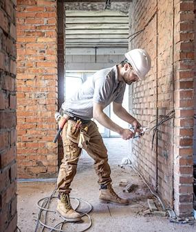 Um eletricista de construção corta um cabo de tensão durante um reparo