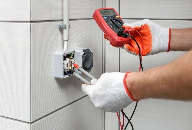 Um eletricista está usando um multímetro para medir a tensão em uma tomada.