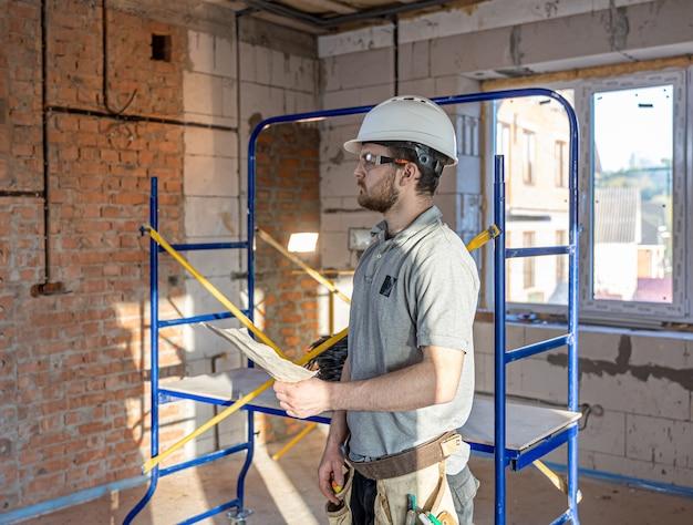 Um eletricista examina um desenho de construção em um local de trabalho.