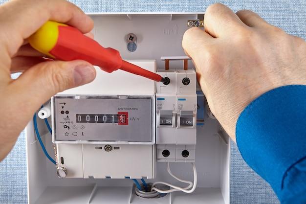 Um eletricista instala um quadro elétrico com disjuntores e medidores de eletricidade.