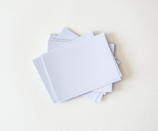 Um empilhamento de maquete vazio cartão branco sobre fundo branco papel