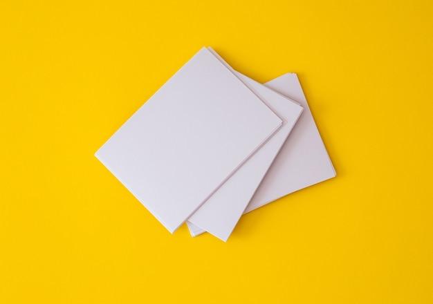 Um empilhamento de maquete vazio cartão branco sobre um fundo amarelo vibrante