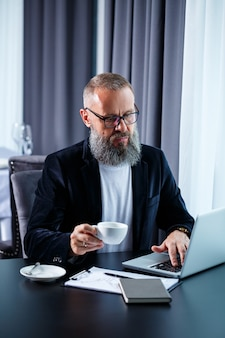 Um empresário adulto do sexo masculino está trabalhando em um novo projeto e olhando para os gráficos de crescimento das ações. senta-se à mesa perto da grande janela. olha para a tela do laptop e bebe café.