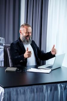 Um empresário adulto do sexo masculino está trabalhando em um novo projeto e olhando para os gráficos de crescimento das ações. senta-se à mesa perto da grande janela. olha para a tela do laptop e sorri