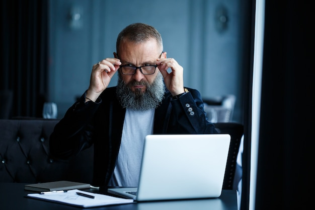 Um empresário adulto do sexo masculino está trabalhando em um novo projeto e olhando para os gráficos de crescimento das ações. senta-se à mesa perto da grande janela. olha para a tela do laptop