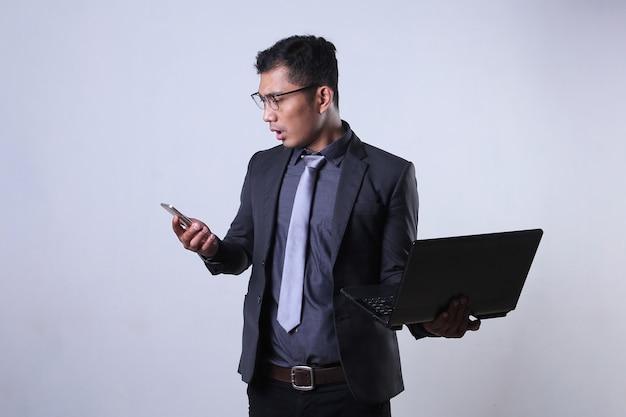 Um empresário asiático parece surpreso ao olhar para um smartphone