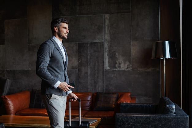 Um empresário atraente vestido formalmente com uma mala moderna e um telefone celular no saguão do hotel. ele está em viagem de negócios e espera o voo da manhã. viagem, simpósio