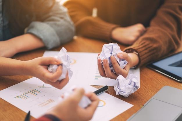 Um empresário bagunçou os papéis à mão com o laptop, o tablet e a papelada na mesa em uma reunião