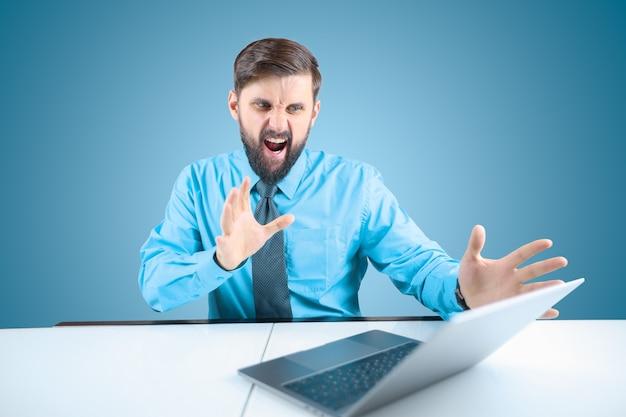 Um empresário barbudo atrás de um laptop estende as mãos e grita, um homem de camisa azul mostra as emoções do grito