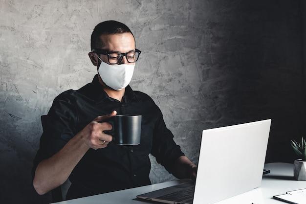 Um empresário com máscara médica trabalha em um computador.