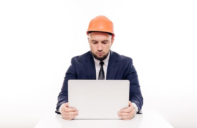 Um empresário construtor cansado com um capacete laranja olha para a tela do laptop e estuda o projeto de construção. senta-se à mesa e bebe café, nervoso