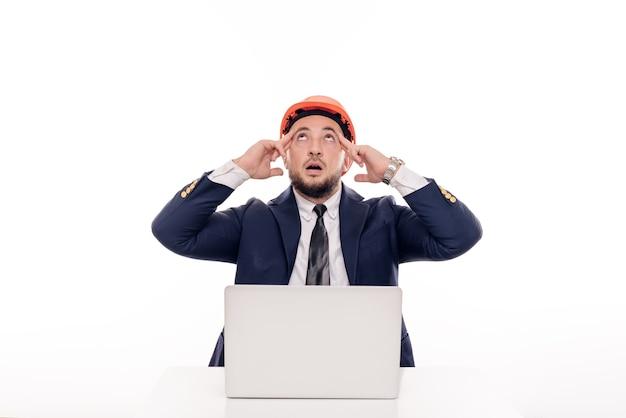Um empresário construtor cansado com um capacete laranja olha para a tela do laptop e estuda o projeto de construção. senta-se à mesa e bebe café, nervoso Foto Premium