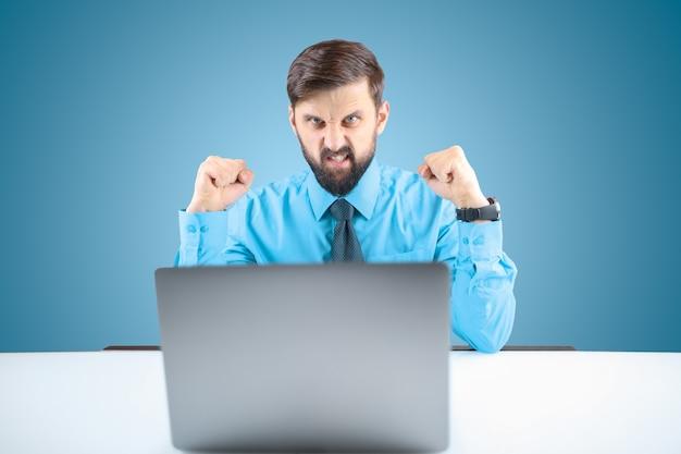 Um empresário de camisa azul cerra os punhos e mostra agressivamente pronto para atacar, um homem com barba atrás de um laptop está pronto para atacar