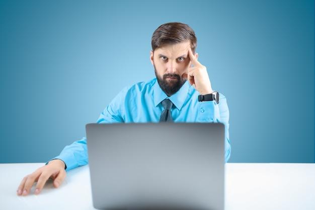 Um empresário de camisa azul e gravata está trabalhando pensativamente em um computador em um projeto responsável. o homem colocou a mão na cabeça, pensando no trabalho