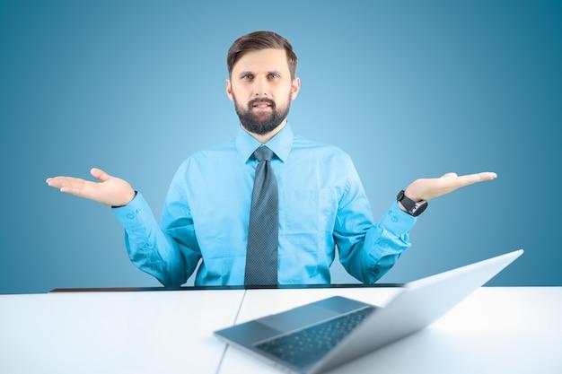 Um empresário de camisa azul e gravata mostra gestos com as mãos, um homem elegante sentado em um laptop levantou as mãos