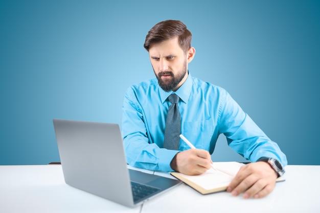 Um empresário de camisa azul e gravata sentado em um laptop escreve tarefas em um caderno com uma expressão relaxada no rosto