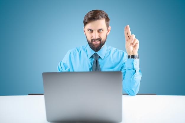 Um empresário de camisa azul levanta as mãos e mostra dois dedos, um homem barbudo no escritório em frente ao computador