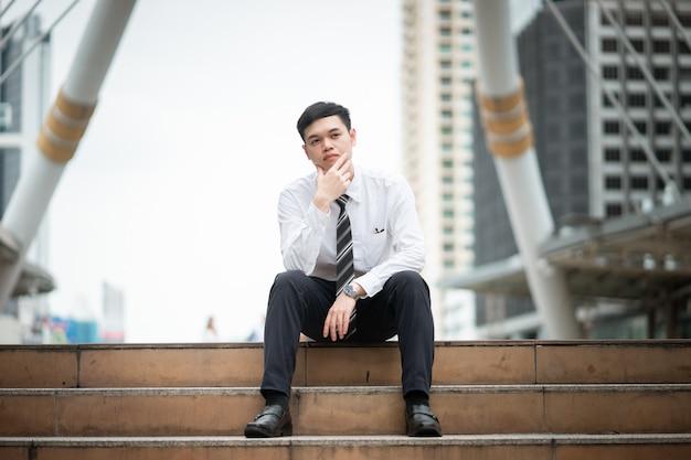 Um empresário de camisa branca está sentado na escada.