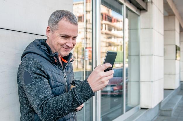 Um empresário de meia idade andando ao lado do prédio de escritórios enquanto usa seu smartphone
