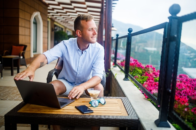 Um empresário de sucesso está sentado a uma mesa com um laptop, ele está trabalhando nas férias. férias e trabalho remoto. o cara está sentado em um restaurante em um terraço com vista panorâmica