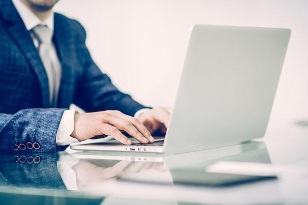 Um empresário de sucesso trabalhando em um laptop no local de trabalho