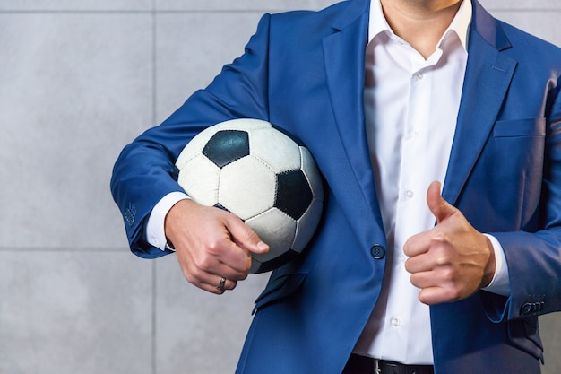 Um empresário de terno azul fica perto da parede e tem uma bola de futebol na mão.