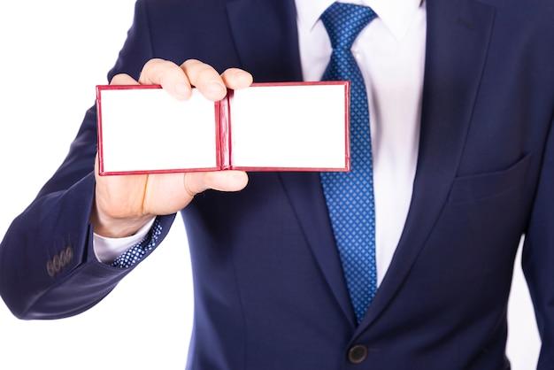 Um empresário de terno azul mostra um cartão de visita ou passe