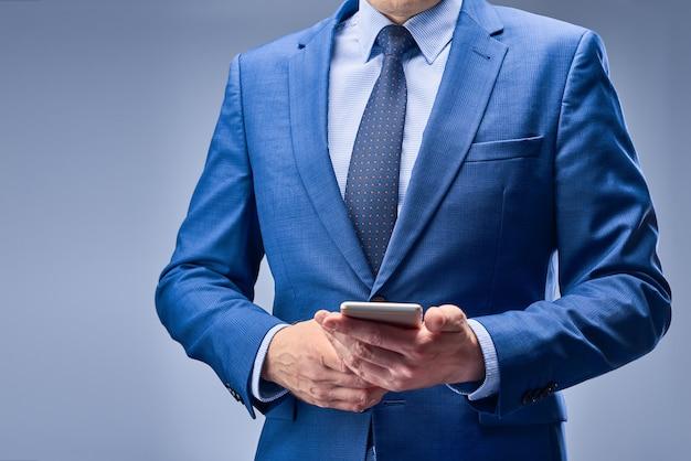 Um empresário de terno azul, segurando um telefone móvel