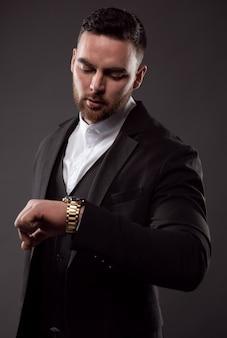 Um empresário de terno preto olha para as horas em seu relógio de pulso.