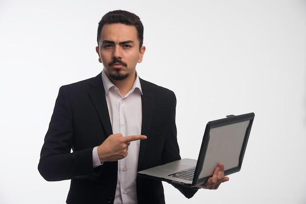 Um empresário em código de vestimenta segurando um laptop e apontando para ele.