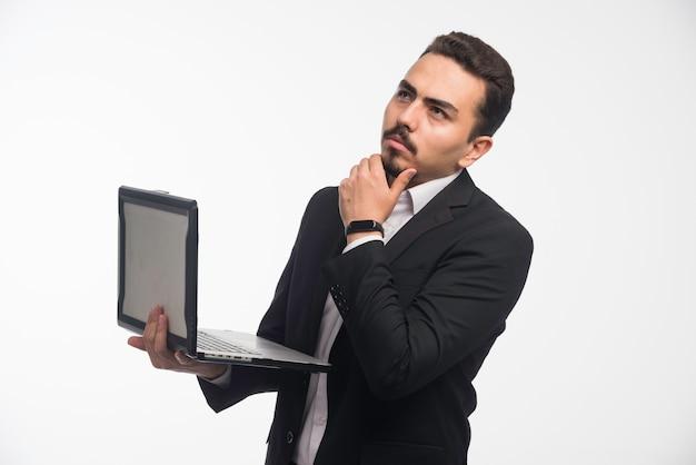 Um empresário em código de vestimenta segurando um laptop e pensando.