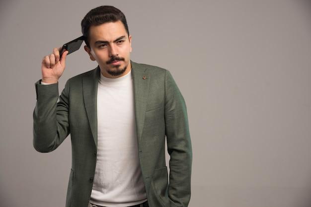 Um empresário em código de vestimenta, verificando seu telefone e ouvindo mensagem de voz.