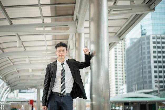 Um empresário em uma camisa branca com gravata e terno preto está de pé ao lado do post.