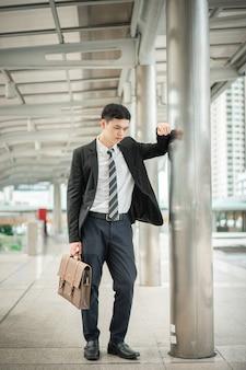 Um empresário em uma camisa branca com gravata e terno preto está segurando uma bolsa.