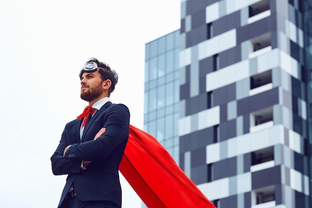 Um empresário em uma fantasia de super-herói está contra um plano de fundo de construção de negócios.