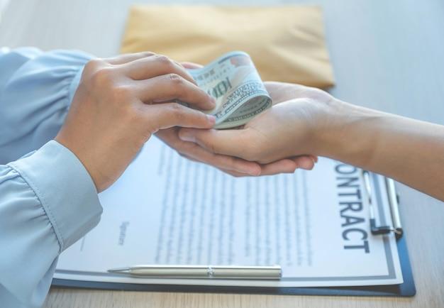 Um empresário entrega dinheiro de suborno aos funcionários para assinarem um acordo comercial